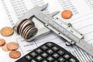 Imagem mostra algumas moedas sendo apertadas por uma chave, para o consumidor conseguir pagar suas dívidas e limpar o seu nome