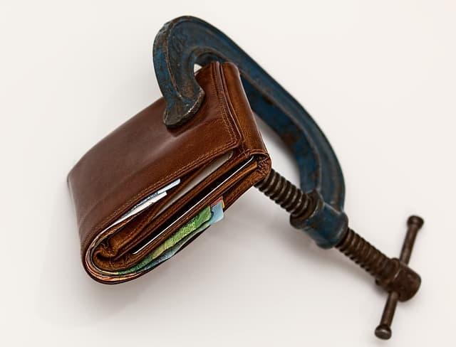 Imagem mostra uma carteira sendo apertada, simbolizando um problema financeiro e possível individamento